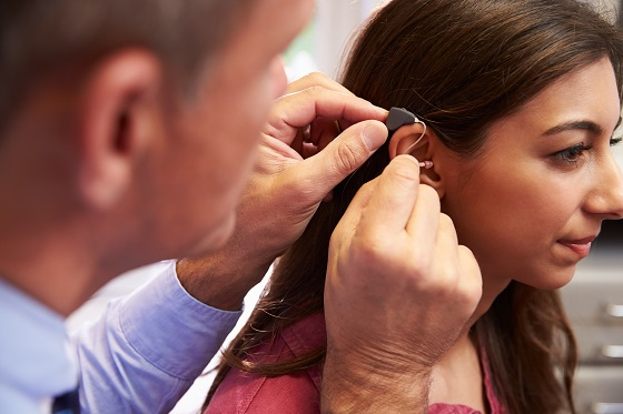 Doctor Fitting Female Patient With Hearing Aid